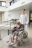 Child in neck brace being pushed in wheelchair by doctor