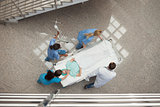 Three nurses and one doctor pushing one patient in a bed