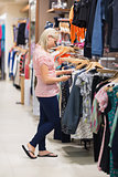 Woman searching for clothes standing in a shop