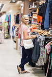 Woman standing in a shop looking for clothes smiling