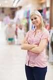 Woman standing in a shop arms crossed