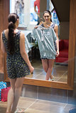 Woman is standing in front of the mirror with clothes