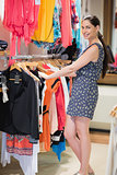Woman is standing at a clothes rack smiling