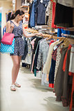 Woman is standing at the clothes rack holding bags