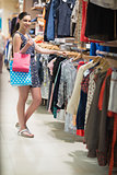 Woman standing at the clothes rack searching