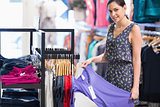 Woman holding purple shirt in clothes store