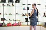 Woman standing beside shoe display