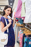 Woman holding clothes showing credit card