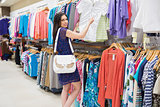 Woman  looking at price tag while holding clothes
