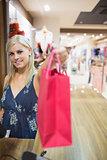 Smiling woman passing shopping bag