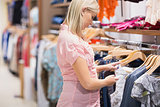 Woman looking though clothes rail
