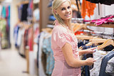 Woman  standing at the clothes rack and smiling