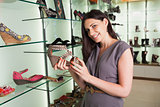 Woman holding shoe and smiling