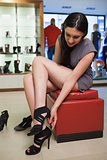 Woman sitting in a boutique trying shoes