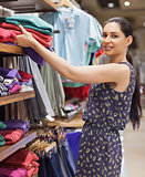 Woman putting jumpers on shelf and smiling