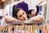 Woman leaning on a clothes rack looking thoughtful