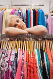 Woman leaning at a clothes rack looking tired