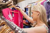 Woman looking at clothes while standing at a clothes rack