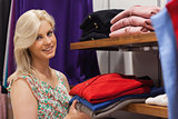 Woman stacking shelf in clothing store