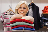 Woman leaning on clothes smiling