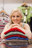 Woman is leaning on clothes and smiling