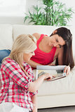 Woman looking at a magazine with friend