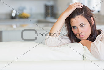 Thoughtful woman sitting on couch