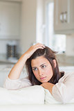 Woman thinking and sitting on couch
