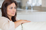 Woman on sofa looking thoughtful