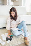 Woman sitting on the carpet checking bills