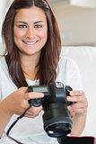 Brunette woman holding digital camera