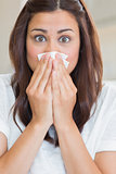 Brunette with runny nose looking surprised