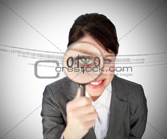Woman looking through magnifying glass at numbers