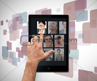 Hand pointing on tablet pc showing photos