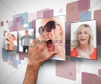 Male hand selecting one photo from digital wall