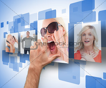 Male hand selecting one of four photos on digital wall