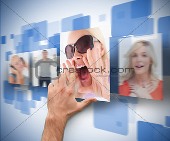 Male hand selecting picture from digital wall