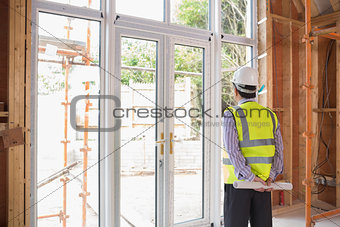 Architect holding a plan while looking outside