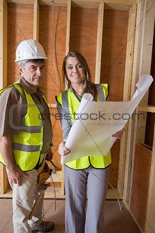 Smiling architects holding blueprints