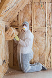 Worker filling walls with insulation