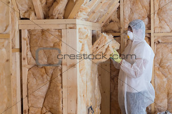 Worker filling walls with insulation material