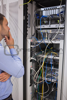 Thoughtful man looking at servers