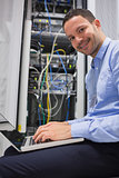 Smiling man using the laptop next to servers