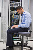Man on his laptop beside servers