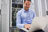 Happy man using laptop to check servers