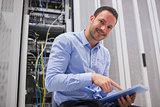 Happy technician working on tablet pc beside servers