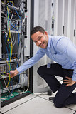 Smiling man adjusting cable in the server