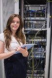 Smiling woman using tablet pc to work on servers