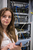 Woman with tablet pc standing in front of servers