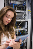 Woman working on servers checking tablet pc